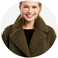Model wears khaki green Teddy Coat from Evans Clothing